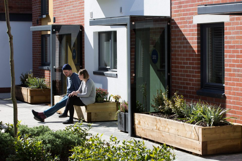 Image of a young couple enjoying the sun outside their house in mixed-use development Paintworks